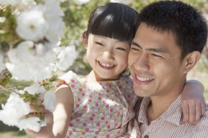 Smiling father and daughter enjoying cherry blossoms on the tree
