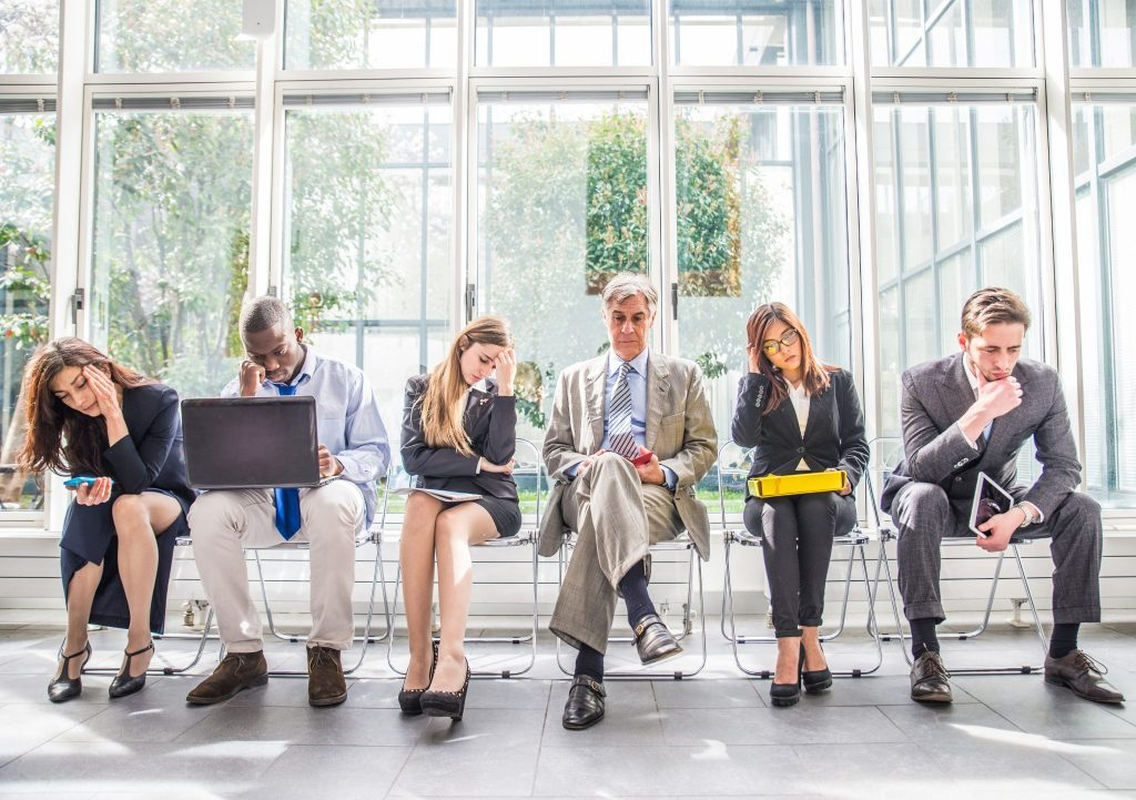 Multiracial group of business people sitting in a waiting room during company's bankruptcy - Depressed and tired team of businessmen waiting for a job interview - Concepts about business bankruptcy crisis and economic depression